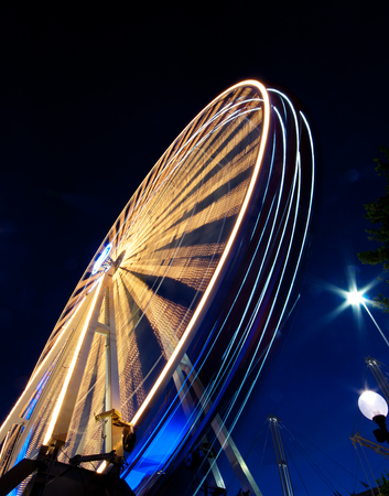 A vibrant Ferris wheel with vivid colours, photographed outdoor with long exposure at twilight. Slow shuts speed motion blur. 版權商用圖片