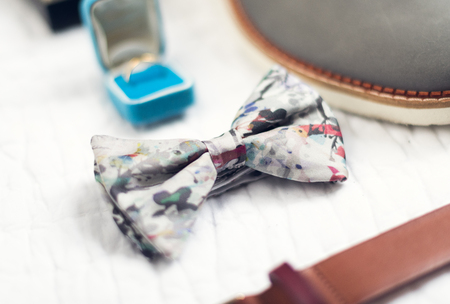 A beautiful bow tie on a white background surrounded by out of focus ring and belt. Shot with an artistic shallow depth of field. Stock Photo