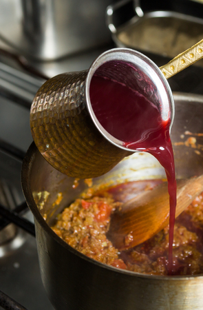 mouth watering: Sweet blended pomegranate sauce being poured into a hot frying pan of ingredients