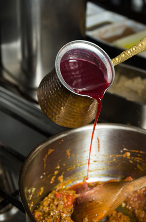 Sweet blended pomegranate sauce being poured into a hot frying pan of ingredients