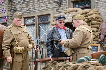 soldiers: Yorkshire, England, 05152015, An group of older british war veteran soldiers checking weapons, from the home guard, with a beret hats and uniform. Howarth 1940s weekend