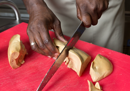 a knife slicing through fresh Foie Gras, on a red cutting board. Stock Photo