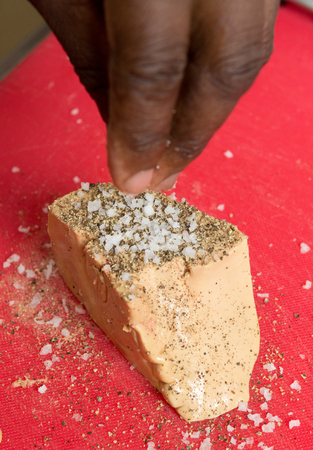 Foie Gras being seasoned with sea salt and black pepper.