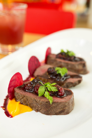 Organic Venison served with fresh raspberry raspberry sauce, beetroot slices and pumpkin puree, on a white plate. Stock Photo