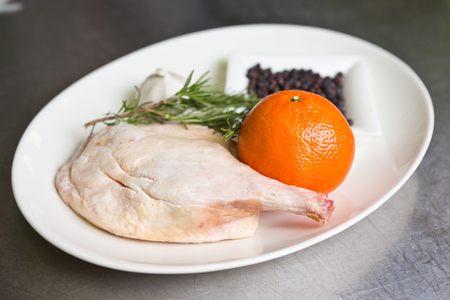 Free range raw duck leg, with herbs, orange and garlic, on a white plate. Duck wellington step by step.