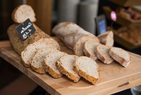 Fresh, warm organic wholemeal bread, with seeds, sliced on a rustic wooden cutting board