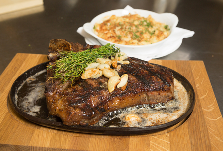 gastro: A grilledT Bone steak, roasted garlic and rosemary on a metal plate, served with Macaroni and cheese.