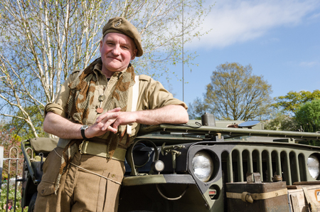 Yorkshire, England, 05152015, An british war veteran soldier with a beret hat leaning agains an army jeep. Howarth 1940s weekend Editorial