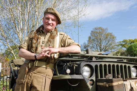 batallón: Yorkshire, Inglaterra, 05152015, un veterano de la guerra soldado británico con un inclinada sombrero de la boina agains un jeep del ejército. Howarth 1940 de fin de semana