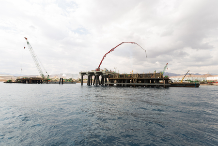 Aqaba, Jordan, 10102015, Construction crane working on a jetty terminal at aqaba new port. Редакционное