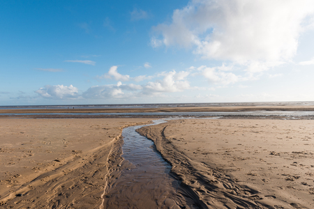 Beautiful blue sky and textured sand, on a cool sunny winters day at the beach
