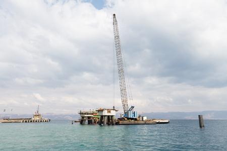 Aqaba, Jordan, 10102015, A crane working on the support foundation construction at the Aqaba new port Редакционное