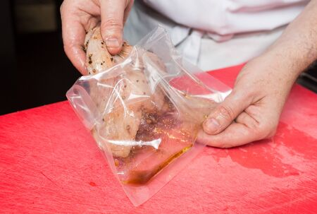 An organic, free range raw duck fillet, being marinated and being placed in an airtight sachet.