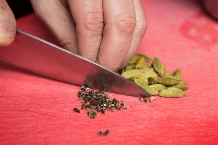 Een mes snijdt grof zwarte peper maïs en kardemon op een rode snijplank. Stockfoto