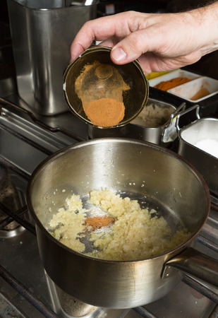 food stuff: Turmeric powder being dropped into a pan of frying  minced garlic and finely sliced onion. Step by step recipe cooking. Stock Photo