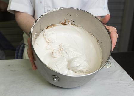 Een mooi rijk en romig, wit geklopt meringue mengsel in een grote metalen mengkom. Stockfoto