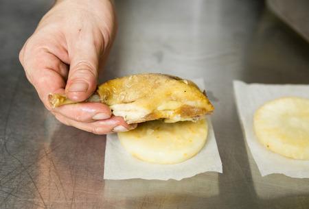 Een gekookte sappige gouden eendpoot van vlees, geplaatst op een gehakte plak knolselderij in een industriële keukenomgeving.