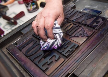 monotype: vintage  wooden antique analogue typeset letter blocks being prepared for block printing.
