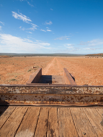 pastoral scenery: Rusty old Australian cattle truck  driving in a sun drenched arid landscape. A rusty cattle trailer against the vibrant famous orange sand and vibrant blue sky in the western Australian desert.