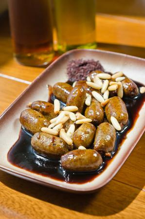 Pittige pan-gebakken mini-kipworsten, geserveerd met een dikke zoete en pittige saus en pijnboompitten.