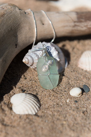 scattering: Unique handmade aqua marine sea glass jewellery, with a silver chain on a rustic sand and driftwood background Stock Photo