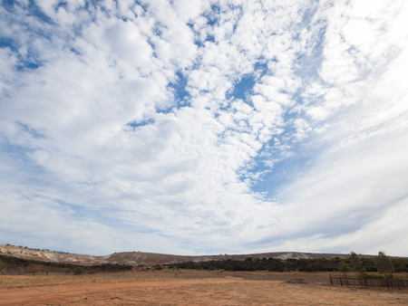 a wide angle shot of the harsh arid red landscape of the australian outback bush, with a cloudy  blue sky backdrop Stock Photo