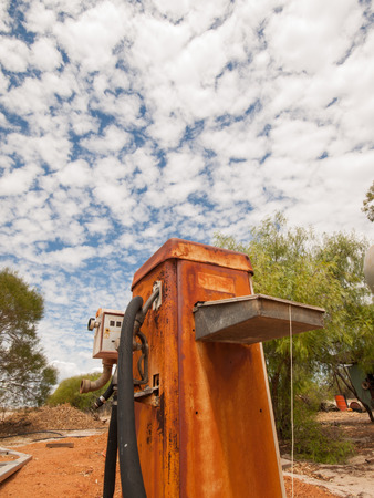 Rusty old australian diesel fuel pump in a sun drenched arid landscape. A rusty fuel pump against the vibrant famous orange sand and vibrant blue sky in the western australian desert. Stock Photo