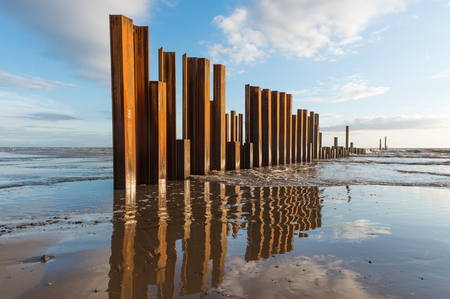 Large rusty steel construction pillars in the sand on a beach, with blue sky and calm waves. The steel girders are rusty.