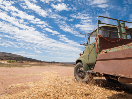 Rusty old australian cattle truck in a sun drenched arid landscape. A rusty cattle van against the vibrant famous orange sand and vibrant blue sky in the western australian desert.