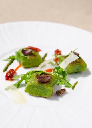 Rijke groene spinazie-polenta, geserveerd met gesneden olijven, rucola, Spaanse peper, zongedroogde tomaat en dunne parmezaanplakken.
