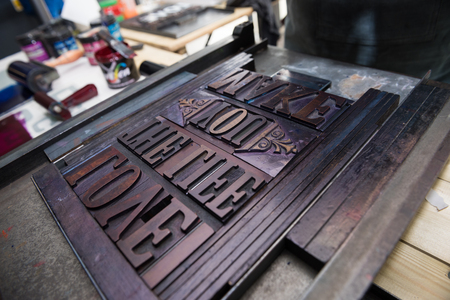 monotype: London, England, 05052017 vintage wooden antique analogue typeset letter blocks being prepared for block printing.
