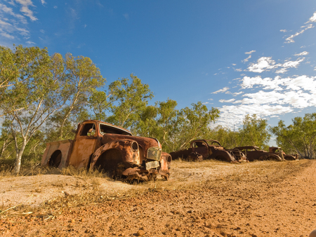 Rusty old australian vehicles in a sun drenched arid landscape. A car graveyard against the vibrant famous orange sand in the western australian desert.