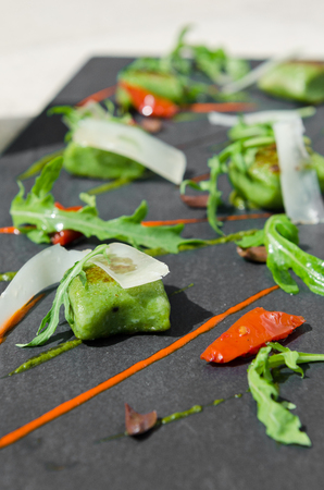 food stuff: Rich green spinach polenta, served with sliced olives, rocket, chilli, sun dried tomato and thin parmesan slices. Served on a contemporary slate plate. Stock Photo