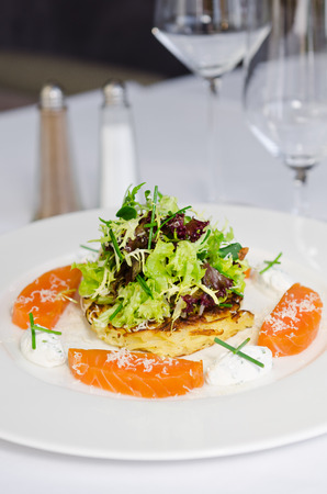beautifully prepared dish consisting of slices of fresh atlantic Salmon fillet, lightly fried potato cake, mozzarella chunks and salad. All served on a clean white plate.