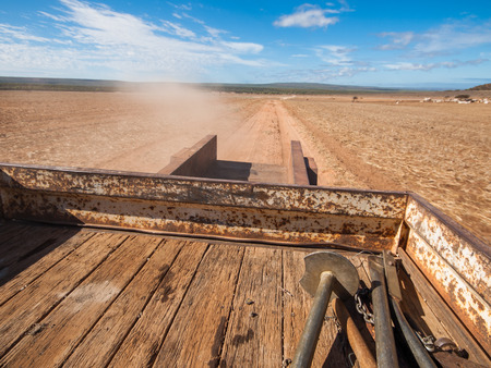 Rusty old Australian cattle truck  driving in a sun drenched arid landscape. A rusty cattle trailer against the vibrant famous orange sand and vibrant blue sky in the western Australian desert.