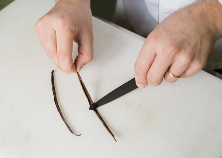 seeding: A vanilla pod on a white chopping board, being scraped by a sharp knife to extract the vanilla essence. Stock Photo