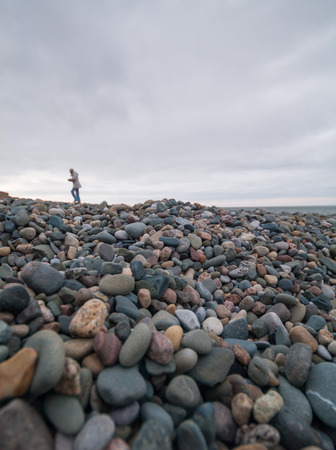 se: A cold grey winters day, at a rocky stone beach with many pebbles. A young girl runs towards the ocean, with a cloudy gloomy sky above. Stock Photo