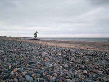 A cold grey winters day, at a rocky stone beach with many pebbles. A young girl runs towards the ocean, with a cloudy gloomy sky above. Stock Photo