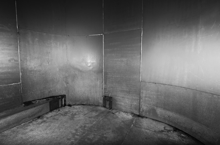 A scary cold futuristic metal sheet prison cell, with a harsh concrete floor. An black and white empty metal prison cell perfect for compositing. Stock Photo