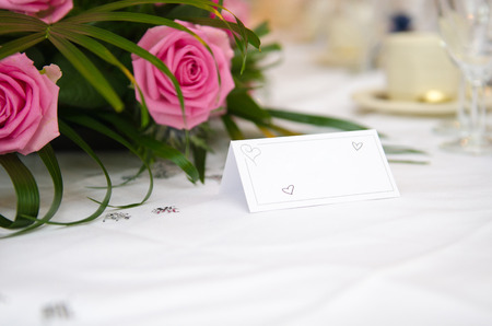 Een leeg blanco papieren tafel kaart naam bord teken op een bruiloft tafel, met mooie roze bloemen geschoten met een ondiepe scherptediepte. Perfect voor het plaatsen van namen in composiet ontwerpen.