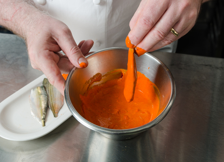 Organic Mackerel fish fillets, being marinated in a metal bowl of vibrant orange tandoori curry spices and sauce, being prepared for further cooking .