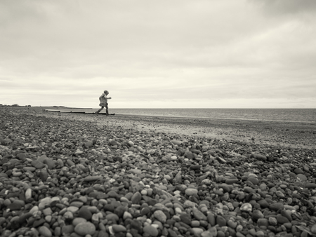 A cold grey winters day, at a rocky stone beach with many pebbles. A young girl runs towards the ocean, with a cloudy gloomy sky above. sepia toned.