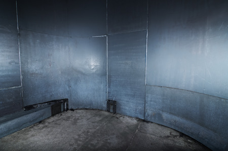 captives: A scary cold  futuristic metal sheet prison cell, with a harsh concrete floor. An empty blue metal prison cell perfect for compositing.