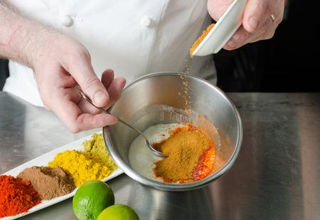 Frische Bio-Tandoori-Gewürz-Zutatenmischung, vermischt und gemischt in einer Metallschale in Vorbereitung für eine Marinade. Standard-Bild - 81672102