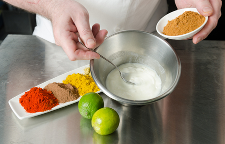 fresh organic tandoori spice ingredient mix, being blended and mixed in a metal bowl in preparation for a marinade. Stock Photo