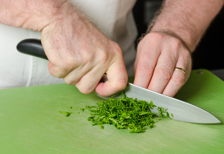A knife, being held by male hands, slicing through fresh organic parsley, on a green vegetable chopping board