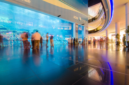 Dubai mall, the largest fish tank aquarium in the world shot with a slow shutter speed with motion blur on the crowd. Stock Photo