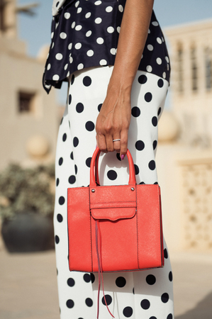 An orange leather designer handbag being held in a females arms. Stock Photo