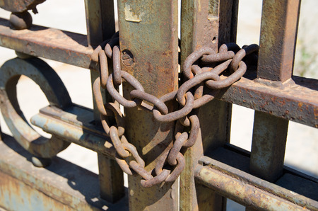 padlock shut off: A rusty old metal chain on some old antique rusty metal gates in the summer sunshine.