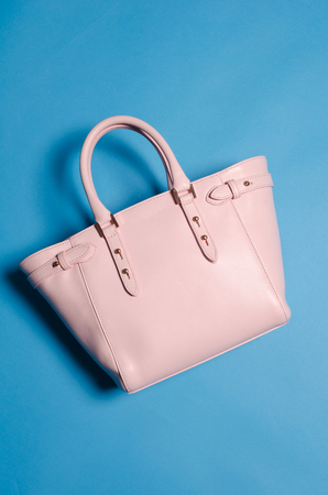 capitalismo: A leather designer handbag, floating against a background, shot in a studio with sharp light and vivid blue and pink colours